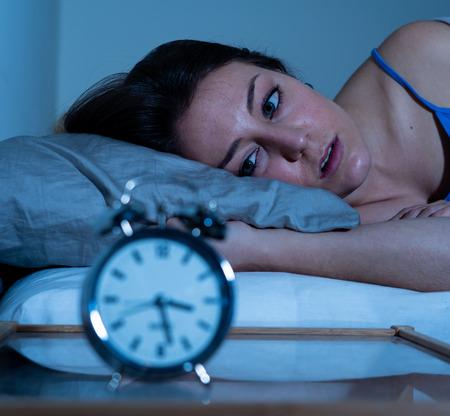 Hermosa mujer caucásica sin dormir y desesperada despierta por la noche sin poder dormir, sintiéndose frustrada y preocupada mirando el reloj que sufre de insomnio en el concepto de trastorno del sueño. Foto de archivo