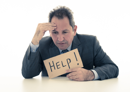 Depressed middle aged caucasian businessman desperate and tired holding a help sign looking frustrated, upset and unhappy. In business and stress at work frustration and unemployment concept.