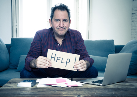 Worried and desperate mature man asking for help in paying off debts and loan calculating bills tax expenses and accounting home finances on couch in Domestic bills and Financial problems concept.