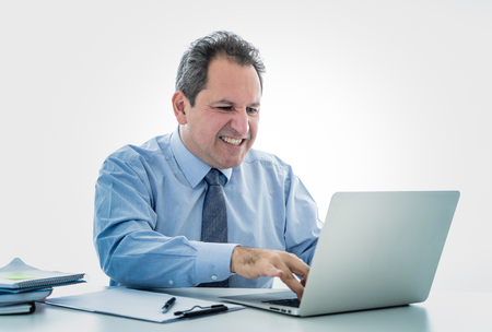 Angry and frustrated middle aged businessman overworked at desk upset with laptop in adults perception and use of technology, Overtime, stress at work concept isolated in white background.