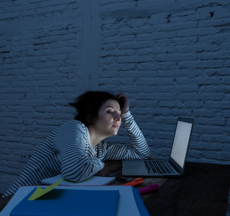 Overworked and tired female student working late at night on her laptop trying not to fall asleep feeling fatigued, worried and sad. Moody dark light. Online learning and stress work concept. Imagens - 119908156