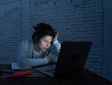 Overworked and tired female student working late at night on her laptop trying not to fall asleep. Feeling fatigued and trying to concentrate and keep on working. In a studying or working concept. 免版税图像