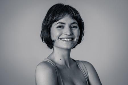 Ciérrese encima del retrato de la mujer bastante caucásica joven atractiva con la cara feliz y la sonrisa hermosa. Aislado en blanco. En Personas, concepto de emociones y expresiones faciales humanas positivas.