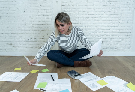 Portrait of worried young woman feeling stressed and desperate on the ground with calculator accounting expenses not able to pay mortgage. In paying debts and domestic bills and financial problems.