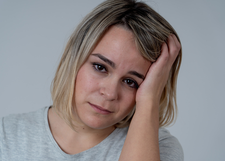 Close up portrait of young sad woman looking worried suffering from headache, Touching her head in pain. In People healthcare, migraines and facial expressions concept. Stock Photo