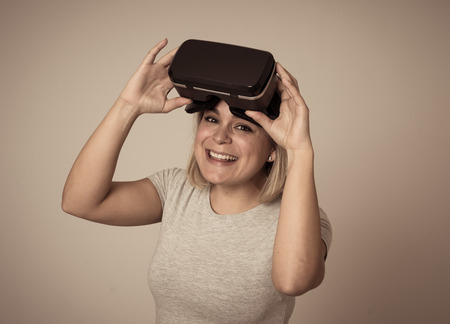 Curious woman happy and excited to use virtual reality goggles feeling excited about simulation, exploring virtual life making happy gestures. In New technology Virtual Augmented Reality concept.