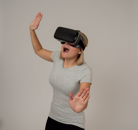 Curious amazed teen woman using augmented or VR goggles, feeling excited about simulation, exploring and interacting with virtual reality making gestures. In new and futuristic technology experiences.