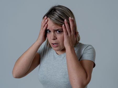 Schließen Sie das Porträt einer jungen Frau, die sich ängstlich und schockiert fühlt und ihr Gesicht vor etwas Beängstigendem versteckt. Schaut mit Angst in ihren Augen. Menschen und menschliche Ausdrücke und Emotionen Konzept. Stimmungsvolles Licht.