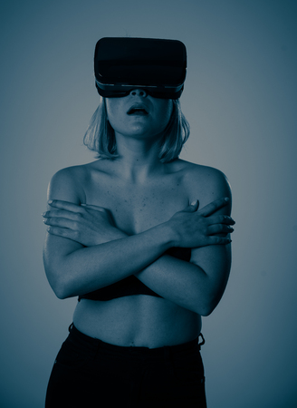 Sensual attractive woman using augmented or virtual reality goggles feeling excited exploring virtual sexuality while getting topless covering her breast. In cyber sex VR simulator and new technology. Banco de Imagens - 121212419