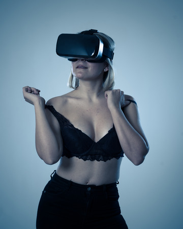 Sensual woman using augmented, virtual reality goggles feeling excited about simulation, exploring virtual sexuality wearing sexy black bra and getting aroused. In Sex and New technology concept. Banco de Imagens - 121212523