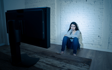 Dramatic portrait of sad scared young woman sitting on the ground staring at computer suffering bullying and harassment. Being online abused by stalker feeling desperate in Internet problem concept.