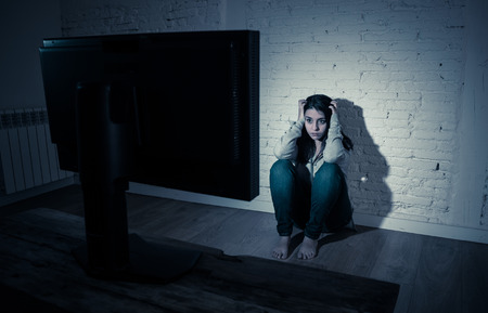 Dramatic portrait of intimidated lonely young woman alone at night staring at computer suffering harassment and cyberbullying. Abused by online stalker feeling desperate. In dangers of Internet.