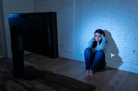 Dramatic portrait of sad scared young woman on the ground staring a computer suffering cyberbullying and harassment. Being online abused by stalker feeling desperate. Dangers of internet concept. Stock Photo - 121212536