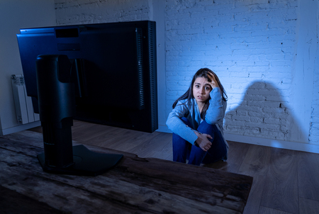 Dramatic portrait of intimidated depressed young woman on ground staring at computer suffering harassment and cyberbullying. Being online abused by stalker feeling desperate. Dangers of in Internet. Stock Photo - 121212601