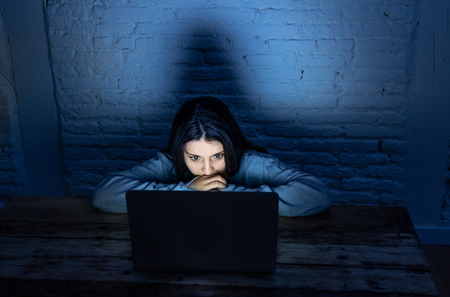 Dramatic portrait of sad, scared young woman on laptop suffering cyber bullying and harassment. Being online abused by stalker feeling desperate, humiliated and intimidated in dangers of Internet.