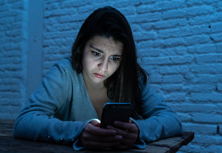 Dramatic portrait of sad scared young woman on smart mobile phone suffering cyber bullying and harassment. feeling lonely, depressed and in fear being online abused by stalker. In dangers of internet. Imagens