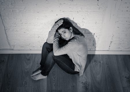 Black and white portrait of young depressed woman feeling desperate, lonely and hopeless on the ground at home. Moody light. In People women mental health, victim of domestic violence and depression.