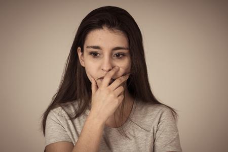 Gros plan sur une jeune femme triste, sérieuse et inquiète, l'air inquiète et réfléchie. Ressentir le chagrin et la dépression couvrant sa bouche. Espace de copie. Dans les expressions faciales et le concept d'émotions humaines.