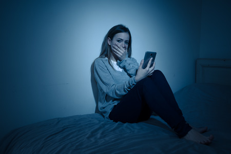 Sad desperate young teenager female girl on smart phone suffering from online bulling and harassment felling lonely and hopeless sitting on bed at night. CYberbullying and dangers of internet concept. Stock Photo - 121213271