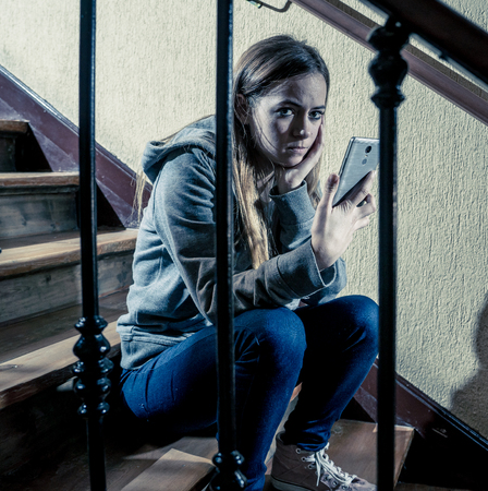 Sad depressed young teenager girl victim of cyberbullying by mobile smart phone siting on stairs feeling lonely, unhappy, hopeless and abused. Bullied by text message on social media app. Dark light Stockfoto