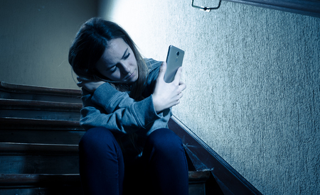 Sad depressed young teenager girl victim of cyberbullying by mobile smart phone siting on stairs feeling lonely, unhappy, hopeless and abused. Bullied by text message on social media app. Dark light Stock Photo
