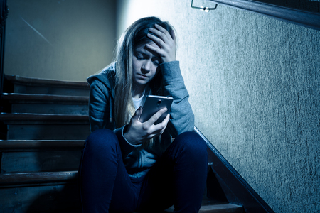 Teenager girl victim of online stalker suffering from cyberbullying abuse feeling lonely and hopeless sitting on stairs with dark light. Dangers of internet, online grooming and harassment concept. Stock Photo