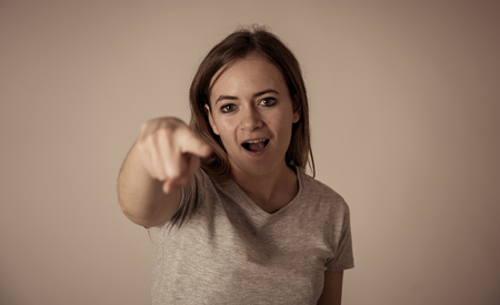 Portrait of angry and upset young teenager girl looking furious threatening and pointing at someone in People and human emotions, facial expressions, education, violence and bullying concept. Stock fotó