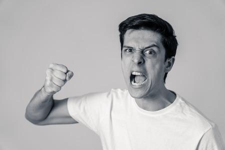 Gros plan noir et blanc d'un jeune homme de race blanche avec un visage en colère. L'air fou, fou, agressif avec le poing serré de colère. Isolé sur fond blanc. Expressions faciales et émotions.