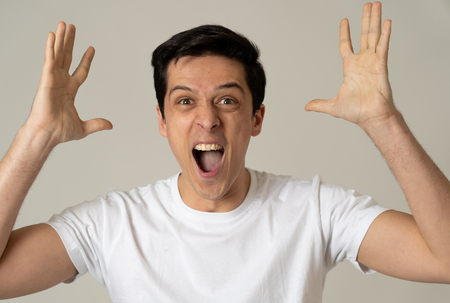 Portrait of young shocked man winning the lottery or having great success with surprised and happy face and gestures. In People, Facial Expression, Human Emotions and celebration. Studio shot.