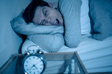 Sleepless and desperate young man awake at night not able to sleep, feeling frustrated and worried looking in distress at clock suffering from insomnia. In mental health, stress and sleep disorder. Imagens