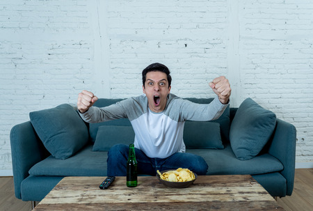 Lifestyle portrait of excited football fan having fun watching soccer or football game on television. Enjoying and celebrating goal and victory drinking beer and eating chips. Sports fans and Goal.