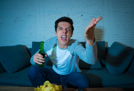 Young man drinking beer at home watching soccer football match or sports game in television at night. Screaming and celebrating goal or victory. In celebration, sports and fans concept.