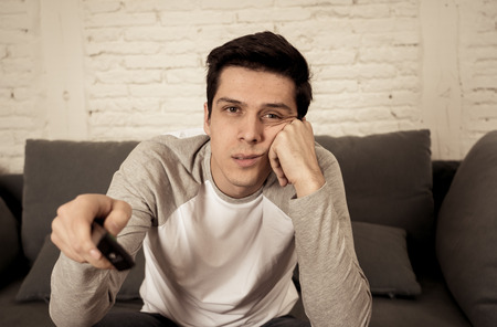 Retrato de estilo de vida de un joven aburrido en el sofá con zapping de control remoto para películas o deportes en vivo. Buscando desinteresado bebiendo cerveza. Adicción sedentaria y masiva a las redes sociales o la televisión.