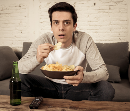 Lifestyle portrait of young man on sofa watching sports or exciting movie on television. Having fun at home enjoying and celebrating goal and victory drinking beer. In entertainment and mass media.