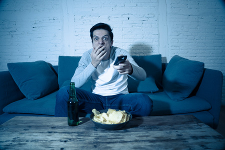 Lifestyle portrait of young scared man watching horror movie or thriller on TV. Holding remote control shocked making frightened gestures. In people, mass media, television and entertainment concept.