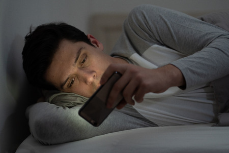 Uzależniony mężczyzna na czacie i surfowaniu w Internecie za pomocą smartfona późno w nocy w łóżku. Znudzony, bezsenny i zmęczony w ciemnym pokoju przy nastrojowym świetle. W koncepcji uzależnienia od bezsenności i telefonów komórkowych.