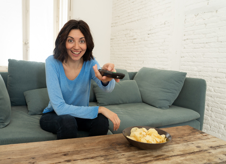 Happy woman on sofa with TV remote control ready to watch favorite movie of TV Show. Looking enthusiastic, making gestures of approval and eating chips. In people, technology and leisure concept.