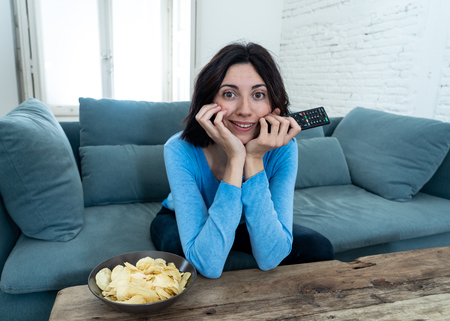 Young happy woman on sofa using TV remote control zapping for another movie or live sport. Looking enthusiastic, making gestures of approval and eating chips. In people, technology and leisure concept.