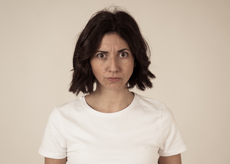 Close up of young frustrated caucasian woman with angry and stressed face. Looking mad and crazy shouting, making hands gestures and pointing at the camera. Copy space. Facial expressions concept.