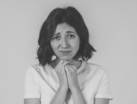 Black and white portrait of young sad woman, serious and concerned, looking worried and disgusted. Staring at the camera with stern look. With copy space. In unhappy emotions and expressions concept.