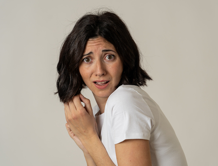 Close up of young woman with frightened eyes, shocked, cowered, cringing. Looking terrified and desperate. People and Human expressions and emotions concept. Isolated on neutral background.