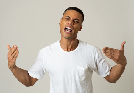 Close up portrait of an attractive young african american man with angry face looking furious and crazy having an argument or fight. In People, Human facial expressions and negative emotions.