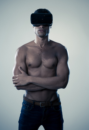 Sensual attractive man using augmented or virtual reality goggles feeling excited exploring new experiences in VR. In VR simulator and new entertainment technology.