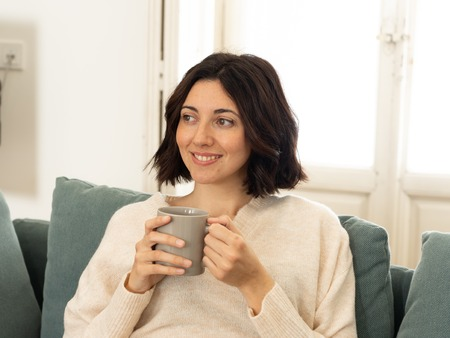 Lifestyle portrait of young pretty relaxed woman drinking hot coffee or chocolate feeling happy and cozy at home smiling happy on the couch. In leisure, peaceful life, happiness lifestyle concept. Stockfoto