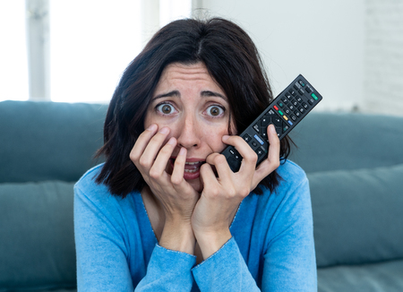Lifestyle portrait of woman feeling scared and shocked making fear, anxiety gestures while watching horror movie on TV holding remote control. In horror and violence on TV and internet and mass media.