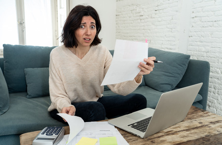 Worried and desperate woman accounting home and business finances on laptop, stressed for too much debts and expenses. In online banking, paying bills mortgage and financial problems concept.