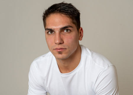 Close up headshot of young mixed race man with natural and neutral face and masculine look. Isolated on neutral background. In People, fashion, lifestyle Beauty and human emotions concept.