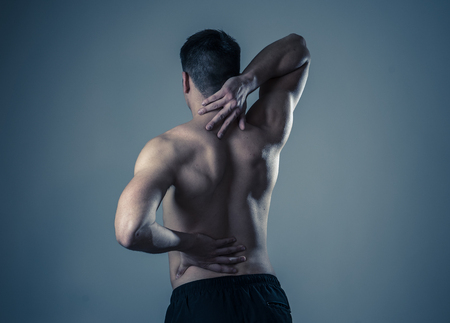 Young muscular fitness man touching and grabbing his neck and lower back suffering cervical pain isolated on neutral background. In sport and workout injury, Incorrect posture problems and body care.