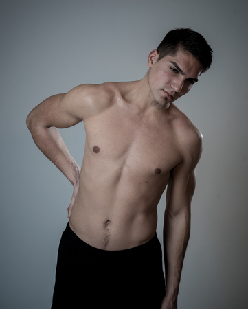 Young muscular fitness man touching and grabbing his lower back suffering strong pain after workout. Isolated on neutral background. In sport injury Incorrect posture problems and body health care.