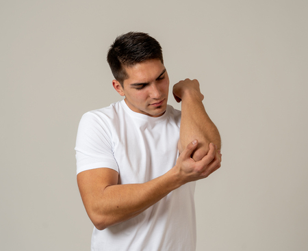Muscular fitness young man touching and grabbing his elbow in pain suffering from an injury isolated on neutral background. In sport injury Pain relief and body health care.